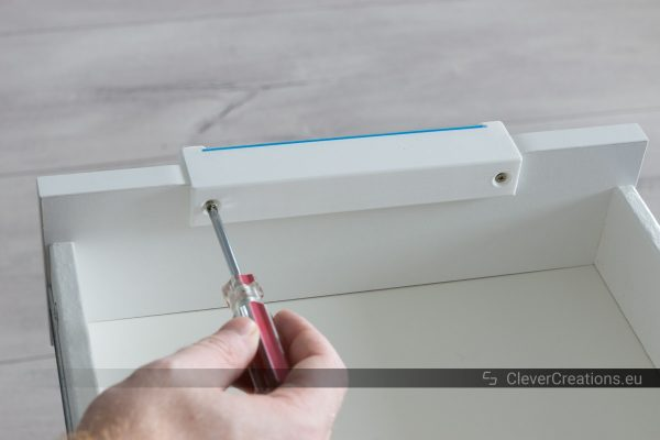 A hand using a screwdriver to drive a screw into an IKEA ALEX drawer to secure a 3D printed handle.