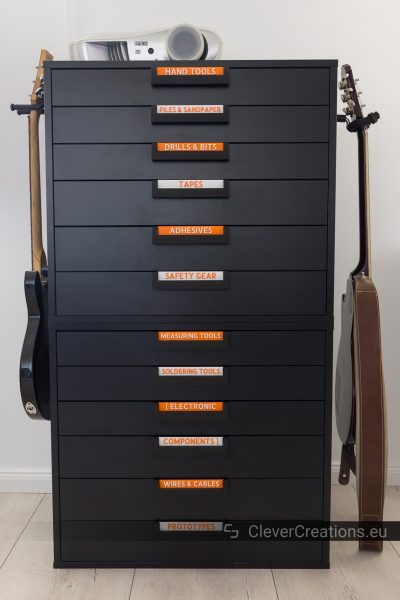Two black IKEA ALEX drawer units stacked on top of each other with 3D printed handles and red labels, on the side of the drawers units are two guitars mounted.