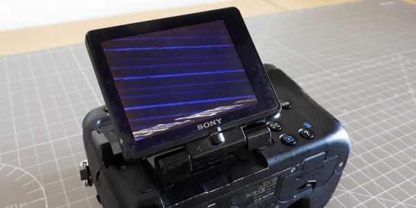 A Sony A77 camera with a broken LCD screen displaying artifacts.