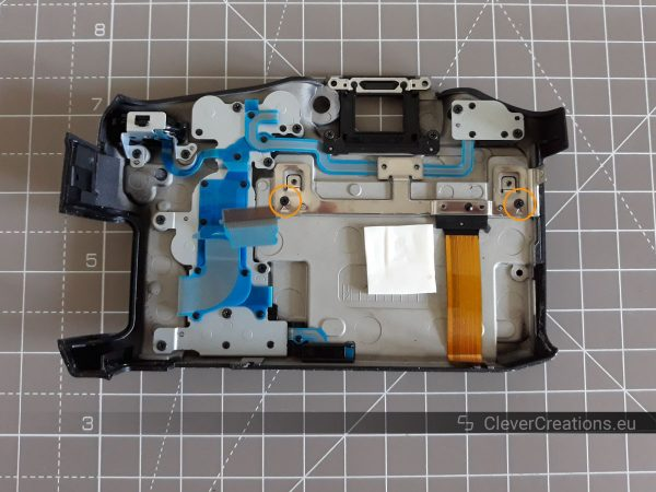 The inside of the rear cover of a Sony SLT-A77 camera. Two exposed screws are circled.