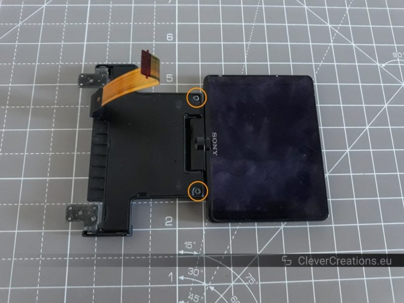 A LCD assembly of a DSLR camera with two exposed screws that are circled.