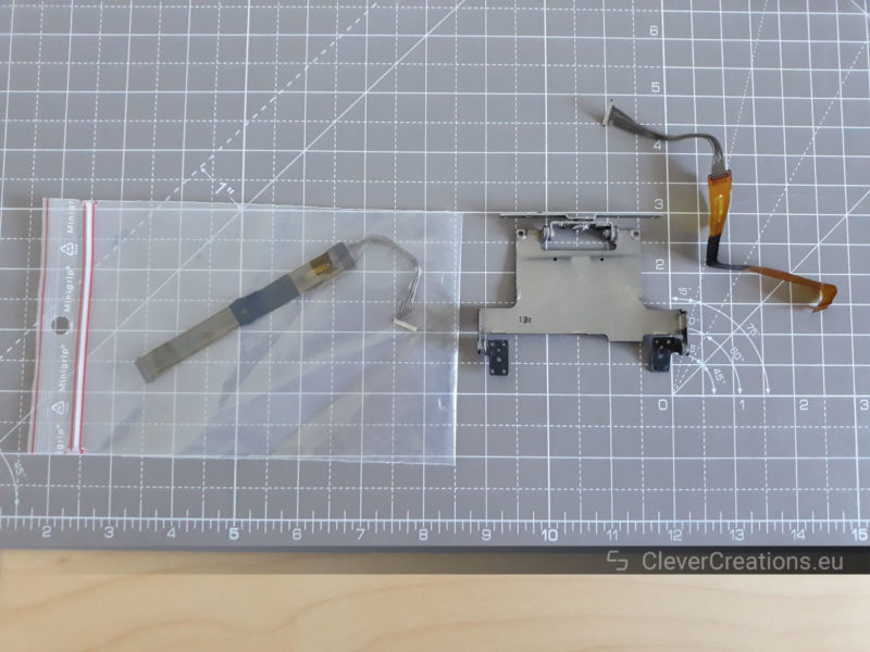 Top view of a metal hinge assembly and two flex cables, one of which is placed in a Ziploc bag.