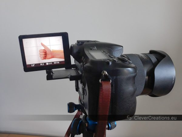 """A Sony A77 camera with a hand signaling """"thumbs up"""" visible on the articulated screen."""