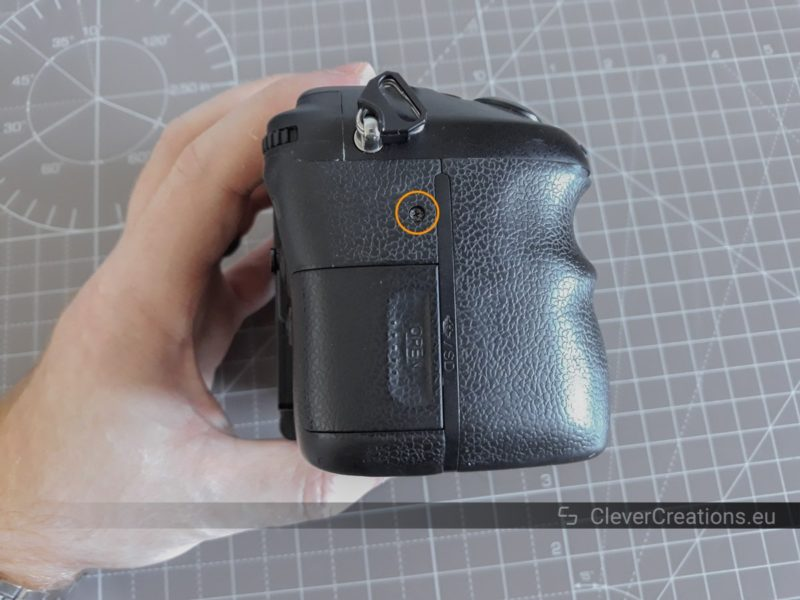 A hand holding up a Sony SLT-A77 camera body. An exposed screw on the side of the camera body is circled.