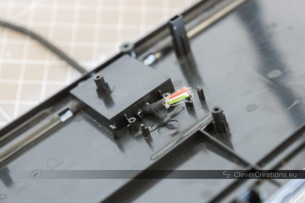 Close-up of a USB cable with exposed wiring that is sticking out of a hole in an element of a computer keyboard.