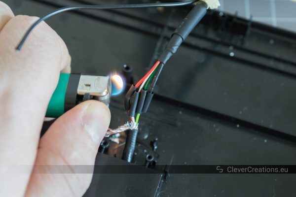 A hand holding a lighter that is being used to shrink four small pieces of heat shrink tubing on the wires of a USB cable.