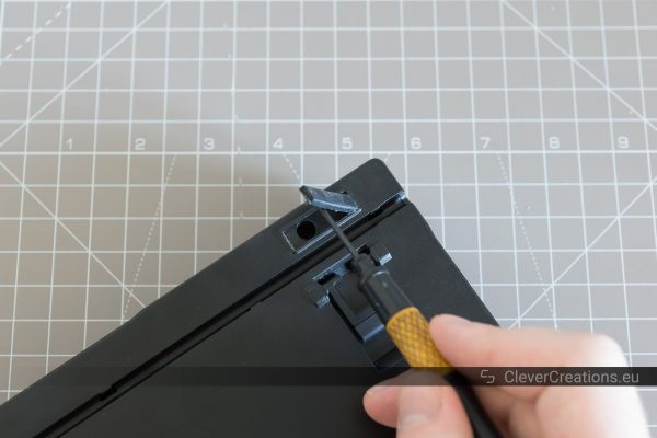 A hand using a screwdriver to lift off the rubber foot from the bottom of a keyboard.