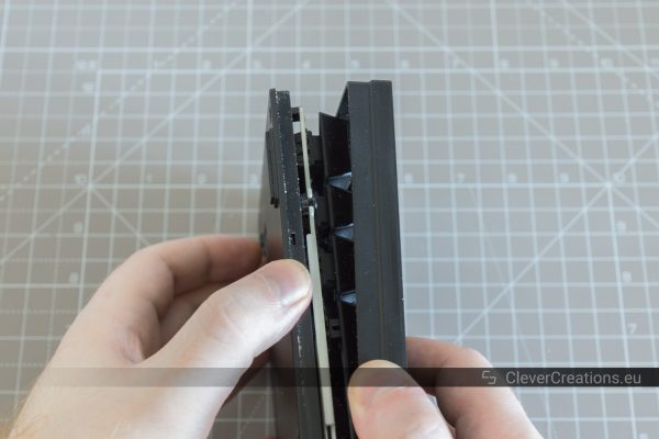 Two hands separating the unscrewed top and bottom halves of a Cooler Master Quickfire keyboard.