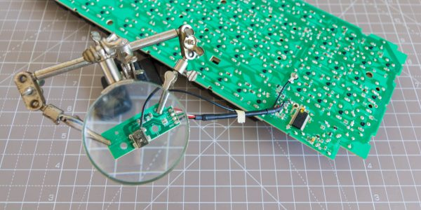 """An exposed PCB of a Cooler Master Quickfire TK Keyboard with a """"third hand"""" tool with a magnifying glass that holds a smaller PCB."""