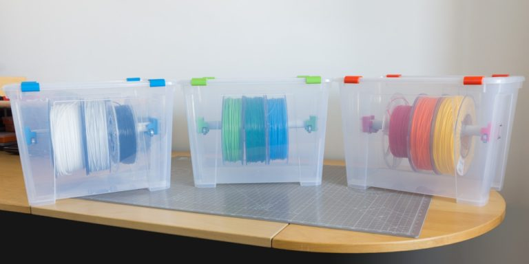 Three 3D printer filament storage boxes containing various rolls of colorful 3D printer filament.