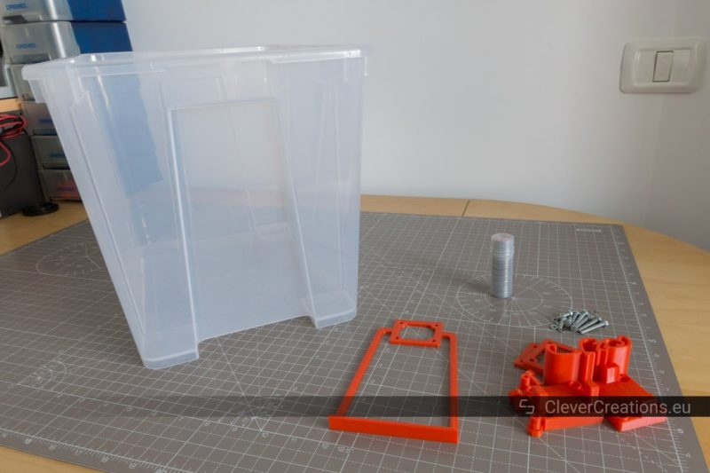 A 22L IKEA SAMLA box with red 3D printed parts for a spool holder assembly placed next to it.