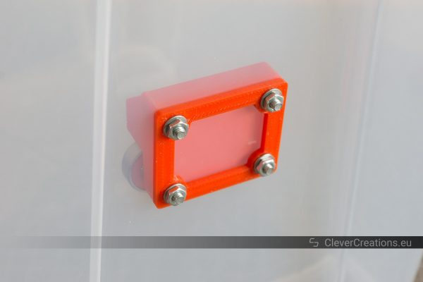 A red plastic assembly that is attached to an IKEA SAMLA box with M4 bolts and nuts.