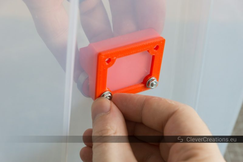 A hand tightening a nut over a bolt that holds together 3D printed parts of a filament storage system assembly.