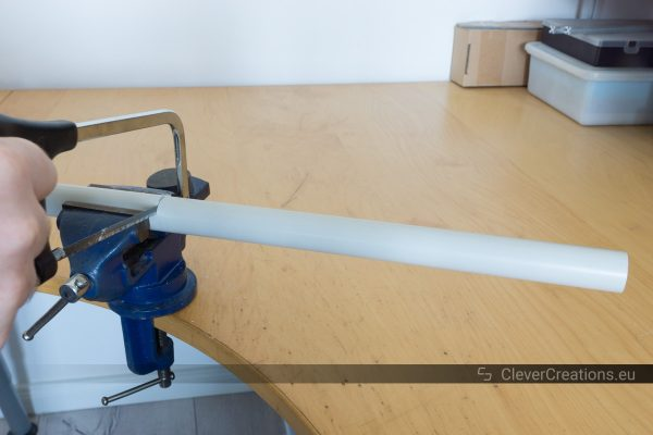 A hand using a hacksaw to cut a grey PVC pipe that is clamped in a vise.