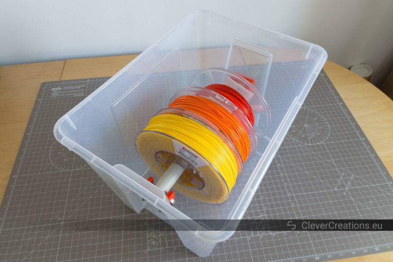 An open IKEA SAMLA box with in it yellow, orange and red 3D printing filament spools on a PVC pipe.