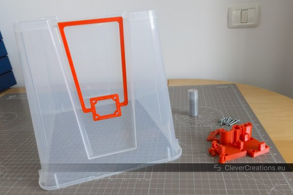 An upside down 22L IKEA SAMLA box with a red drill jig placed on top, with red 3D printed components next to it.