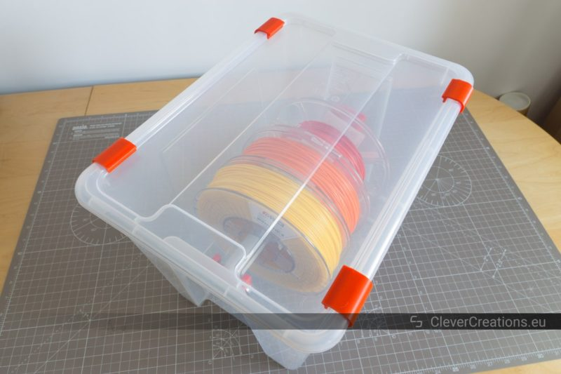 A closed IKEA SAMLA box with in it yellow, orange and red 3D printing filament spools on a PVC pipe.