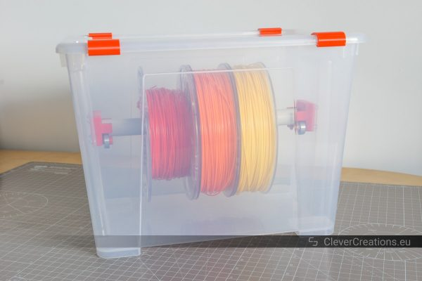 Front view of an IKEA SAMLA box containing yellow, orange and red 3D printing filament spools.