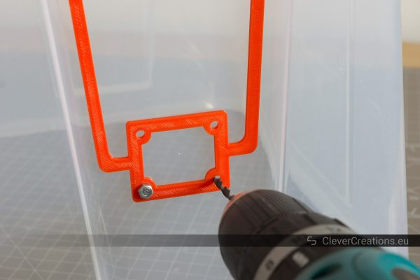 A power drill drilling a hole in a 22L IKEA SAMLA box using a 3D printed red drill jig as a guide.
