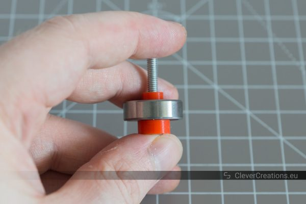 An M4 bolt with a red 3D printed bearing retainer and a 608 roller bearing slid over it.