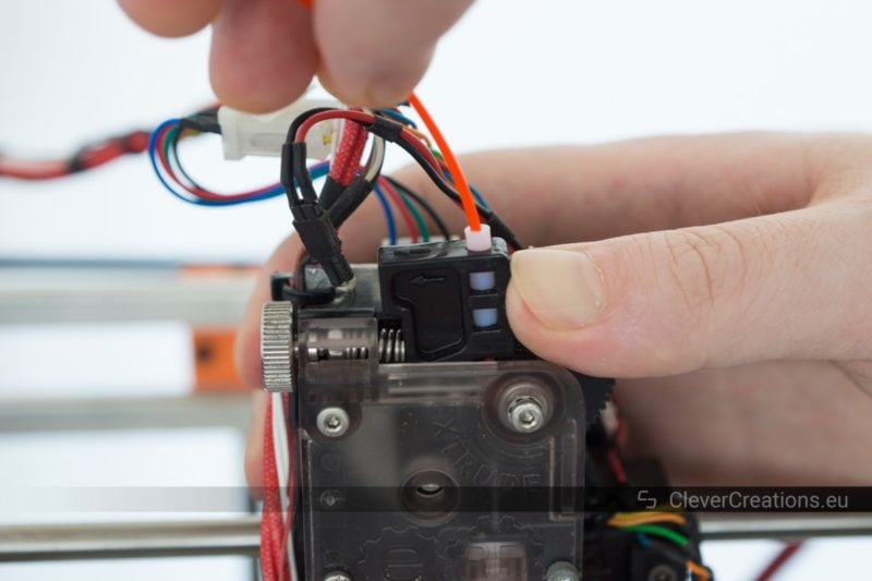 An E3D Titan 3D printer extruder lever being pressed while red filament is being removed from the extruder.