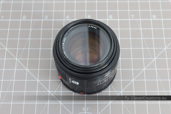 A Minolta/Sony SAL50F14 APS-C camera lens on top of a cutting mat.