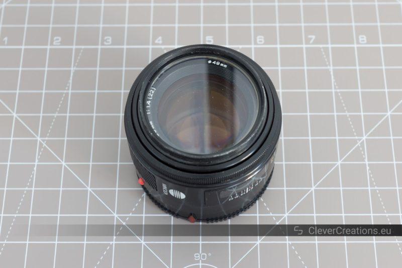 A Minolta/Sony SAL50F14 APS-C camera lens on top of a cutting mat.