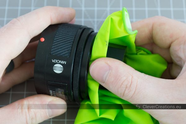 A hand holding a Sony 50mm lens while another hand holds a 3D printed tool against the lens.