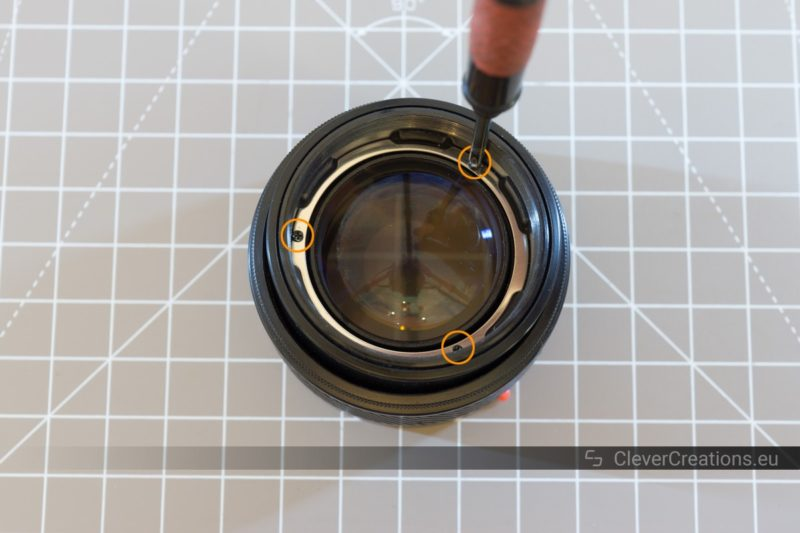 Three circled screws on the inside of a Minolta camera lens, with a screwdriver unscrewing one of the screws.