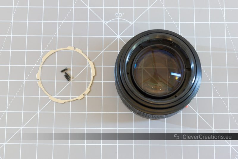 Top view of a partially disassembled lens with some of its components placed next to it.