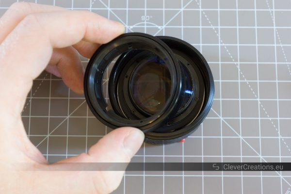 A hand lifting a built-in lens hood out of a partially disassembled camera lens.