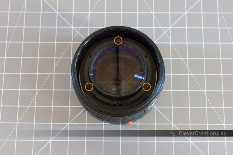 Three circled screws around the front ball lens of a Minolta 50mm camera lens.