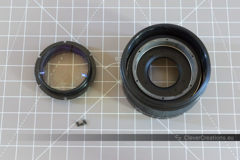 A front ball lens placed next to a partially disassembled camera lens.