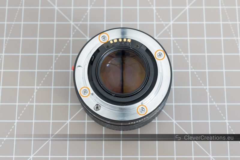 Top view of the rear of a camera lens with four circled screws.