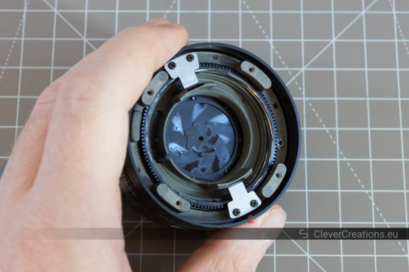 A partially disassembled camera lens with an iris diaphragm with oily aperture blades.