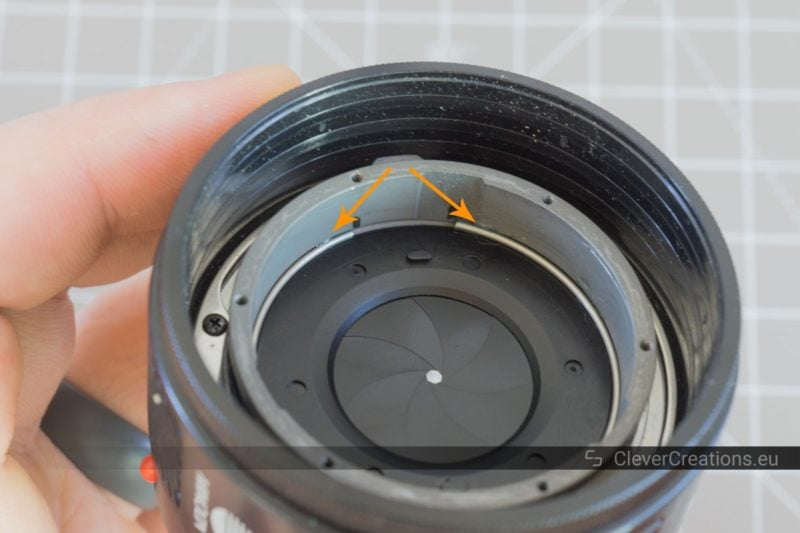 Two arrows pointing at a circular retainer spring on the inside of a camera lens.