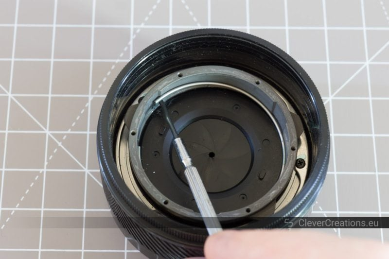 A hand using a small flat-head screwdriver to lift a retainer spring out of a camera lens.