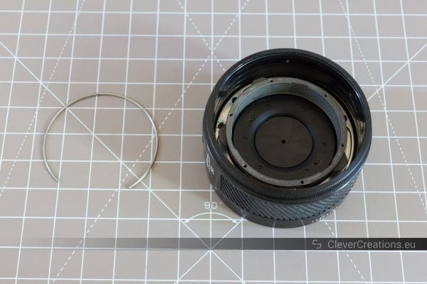 An iris diaphragm retainer spring next to a partially disassembled 50mm prime camera lens.