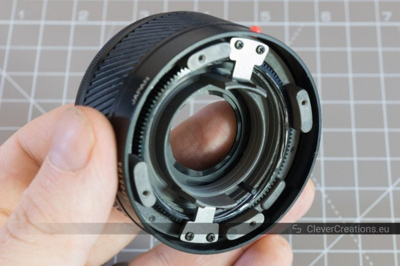 A hand holding a partially disassembled camera lens.