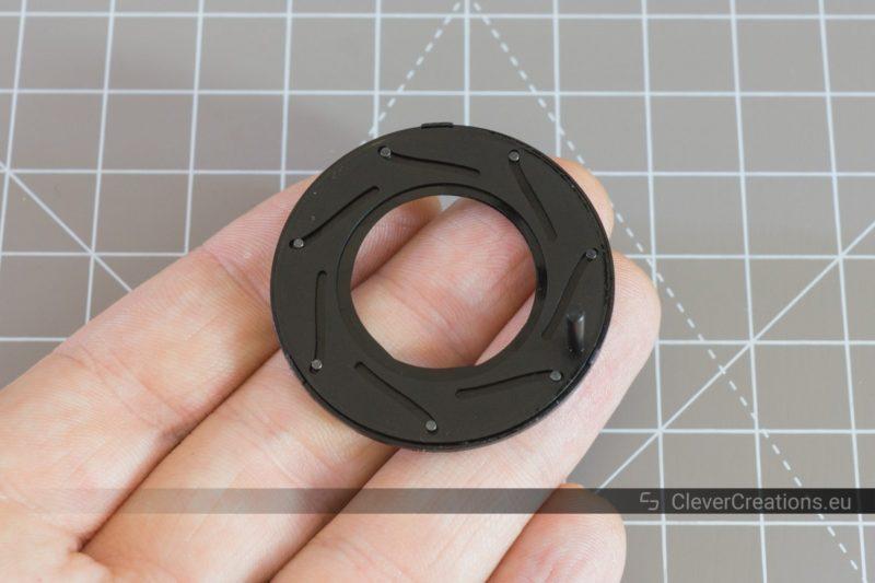 A camera lens iris diaphragm resting on a hand.