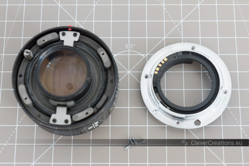 Two components and screws of a partially disassembled camera lens on top of a cutting mat.