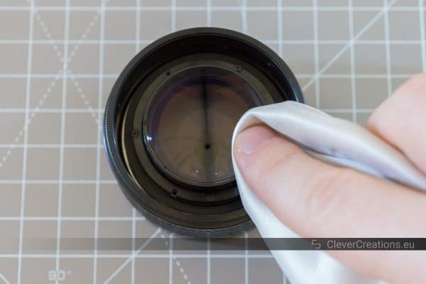 A hand using a microfiber cloth to wipe dust from a lens front element.