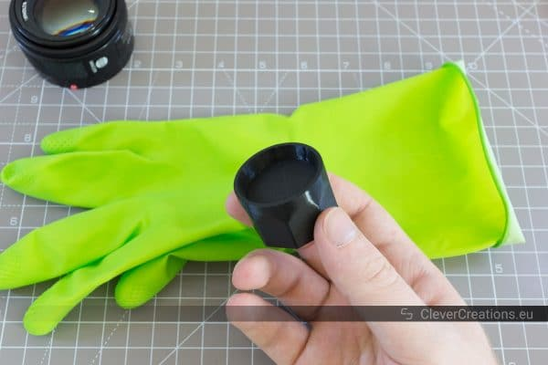 A hand holding a 3D printed camera lens decoration ring removal tool.