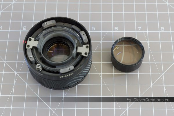 A partially disassembled 50mm prime camera lens with next to its rear ball lens block.