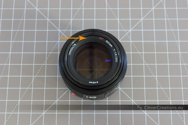 The front of a Minolta 50mm F/1.4 with an arrow pointing to the front decoration ring.