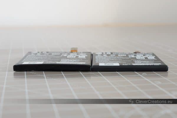 A swollen phone battery next to a new non-swollen battery.