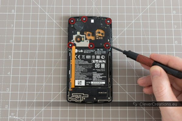 Six circled screws on the inside of a partially disassembled Nexus 5.