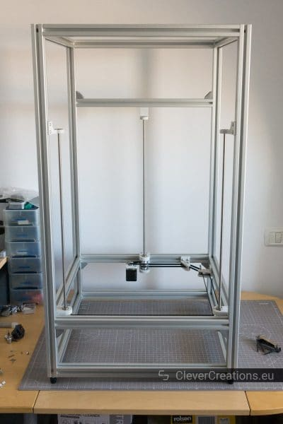 A partially finished 3D printer built out of aluminium extrusion with the majority of the parts of a triple lead screw system assembled inside of it.