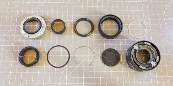 A fully disassembled Minolta Sony SAL50F14 camera lens with all components laid out next to each other on a cutting mat.