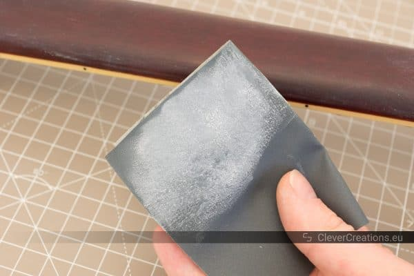 A hand holding a Micro-Mesh sanding sheet covered in white polyurethane lacquer residue.